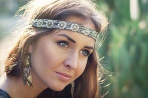 Portrait of a young female hippie with headband and earrings