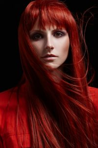 Beautiful portrait of woman with red hair on a black background hair